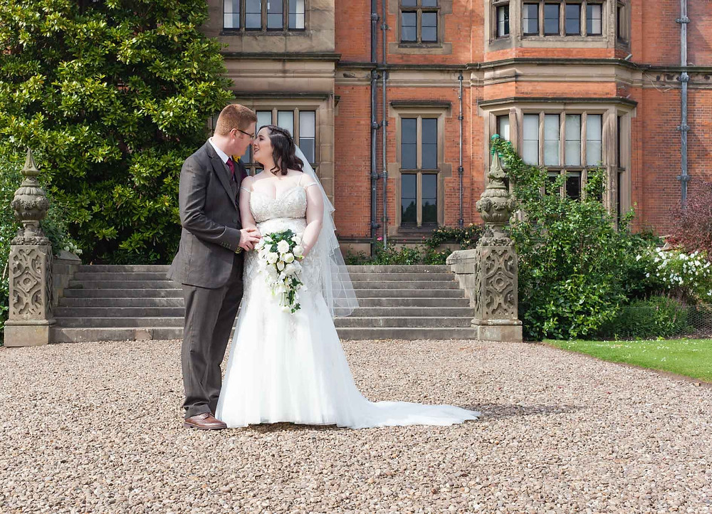 bride and groom sharing a kiss in front of stately home