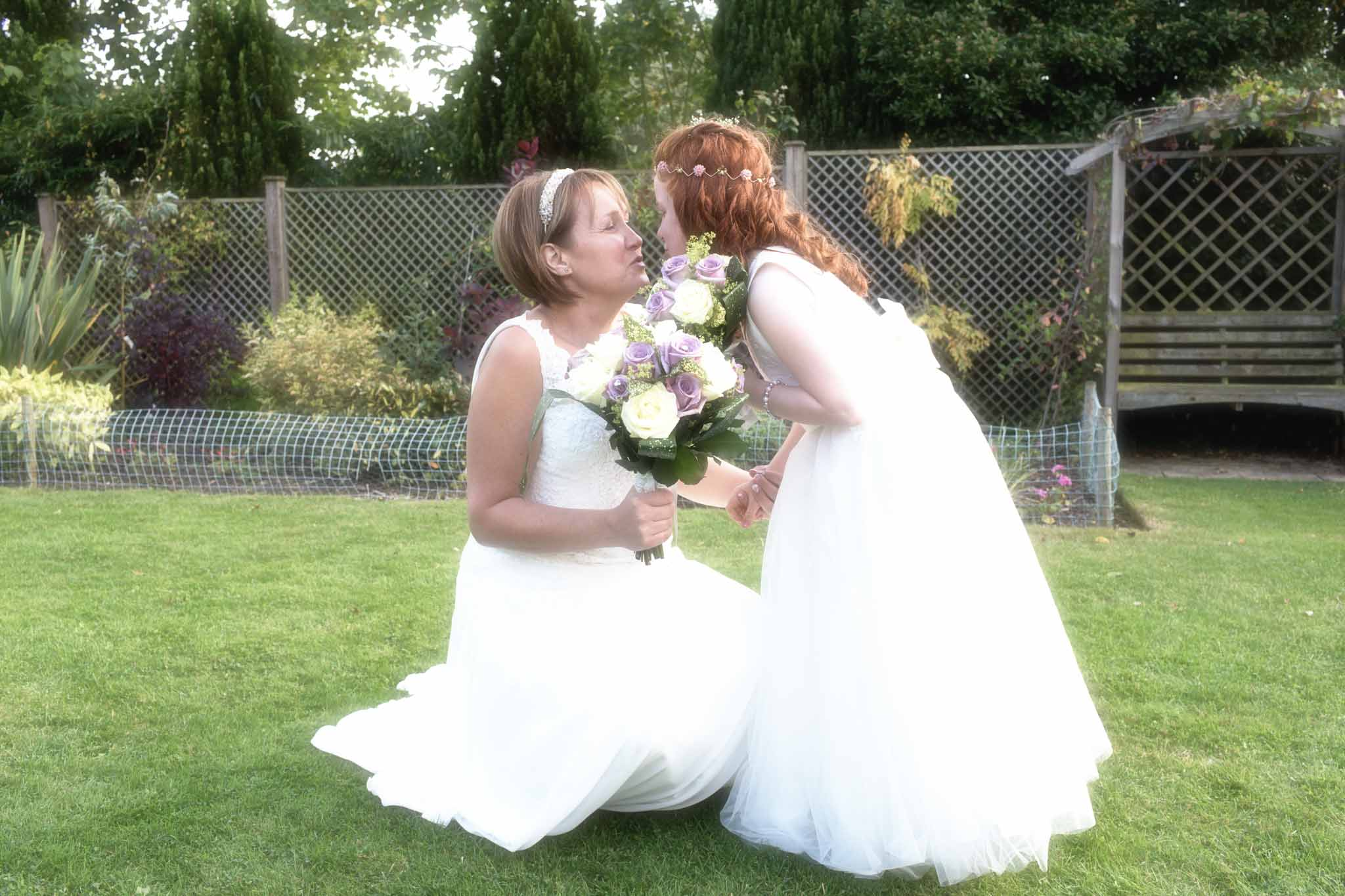 bride holding her bouquet and kneeling down on a grass lawn to kiss her daughter
