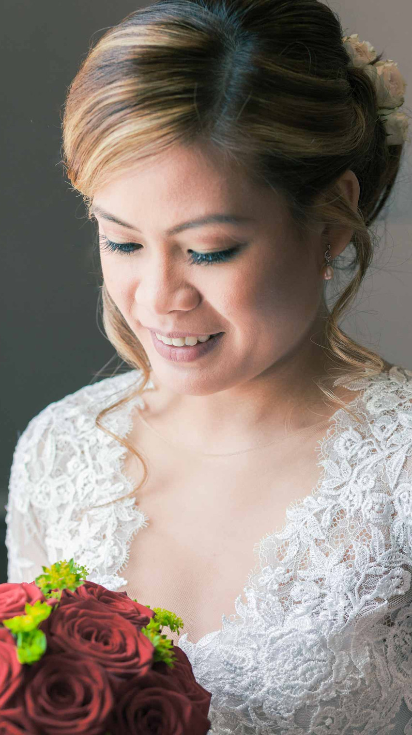 asian bride in a white wedding dress holding her bouquet