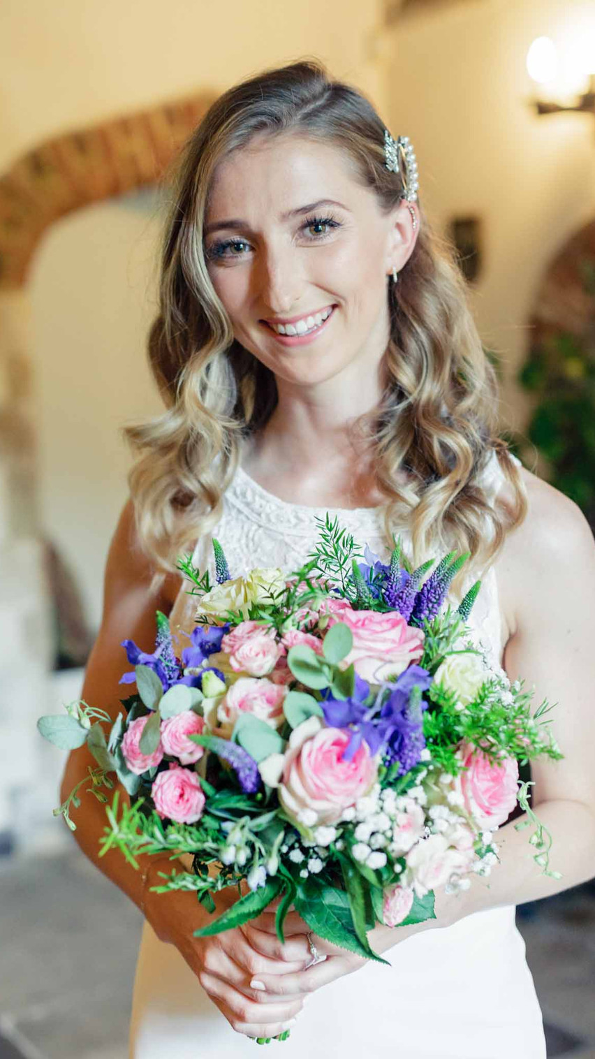 bride in a white dress holds her bouquet looking at the camera