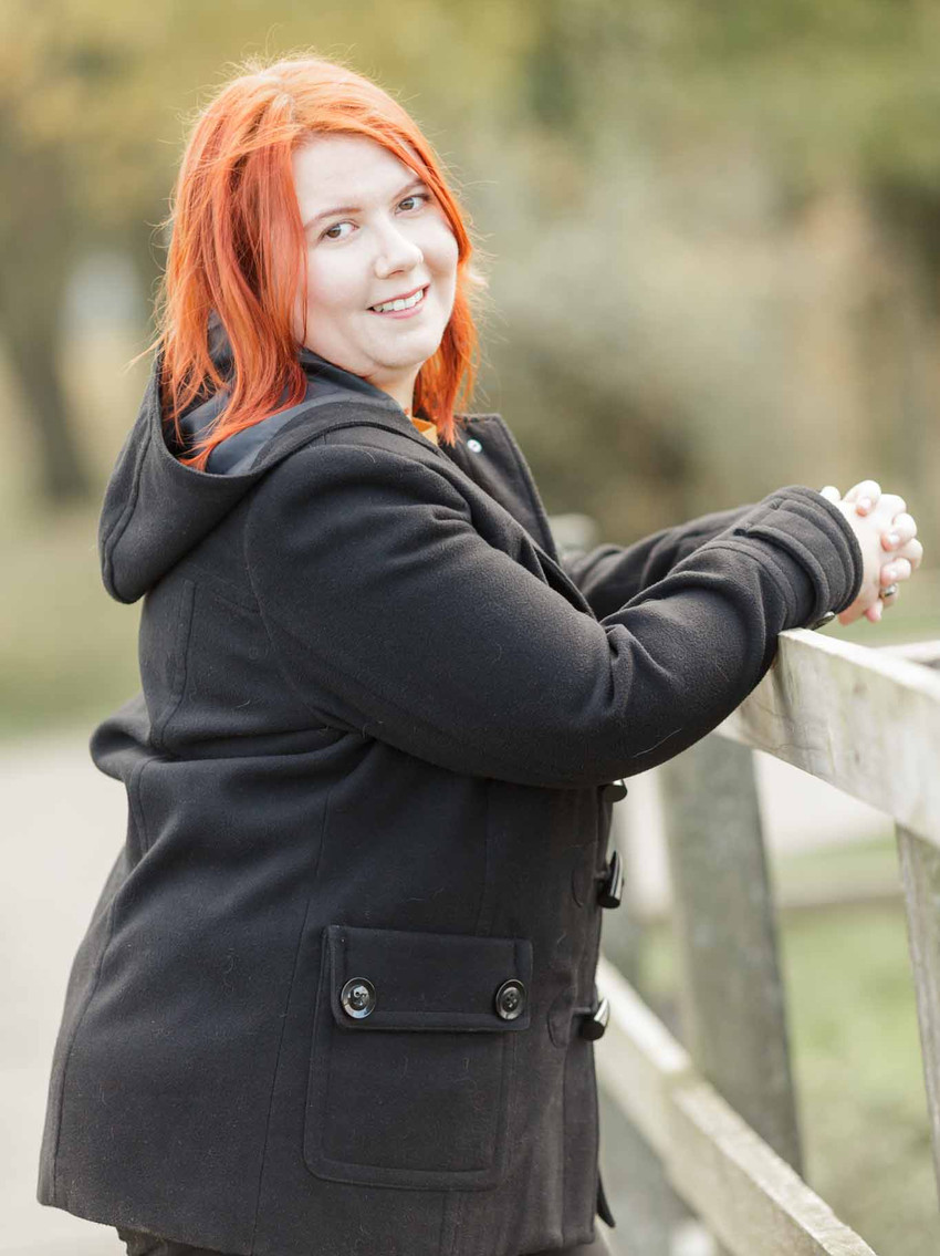 red haired woman looking at the camera in a park
