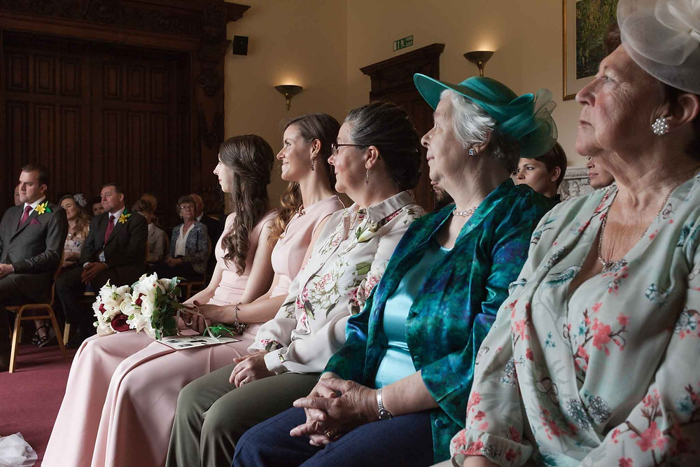 guests look on at bride and groom at the altar