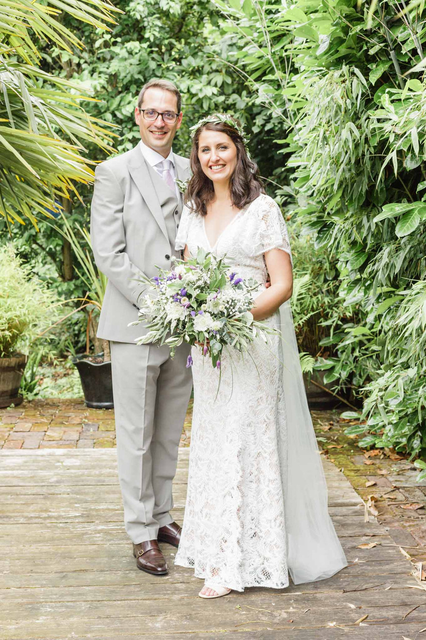 bride and groom standing in a garden holding a bouquet looking at the camera