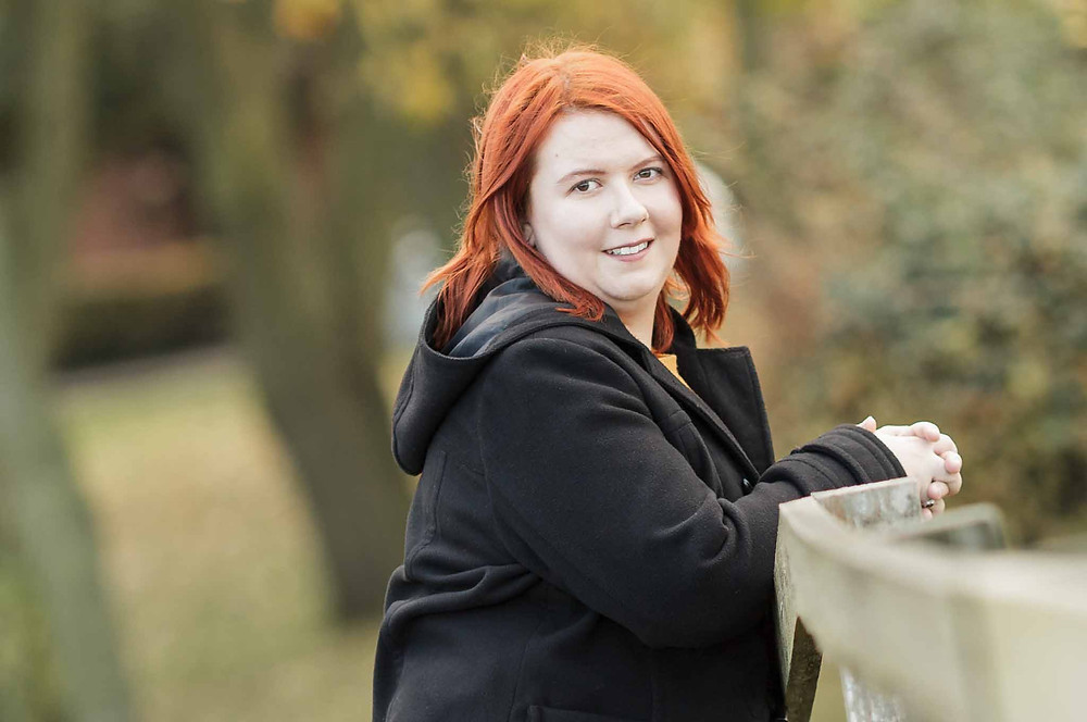 Red haired woman in a park against trees in the background