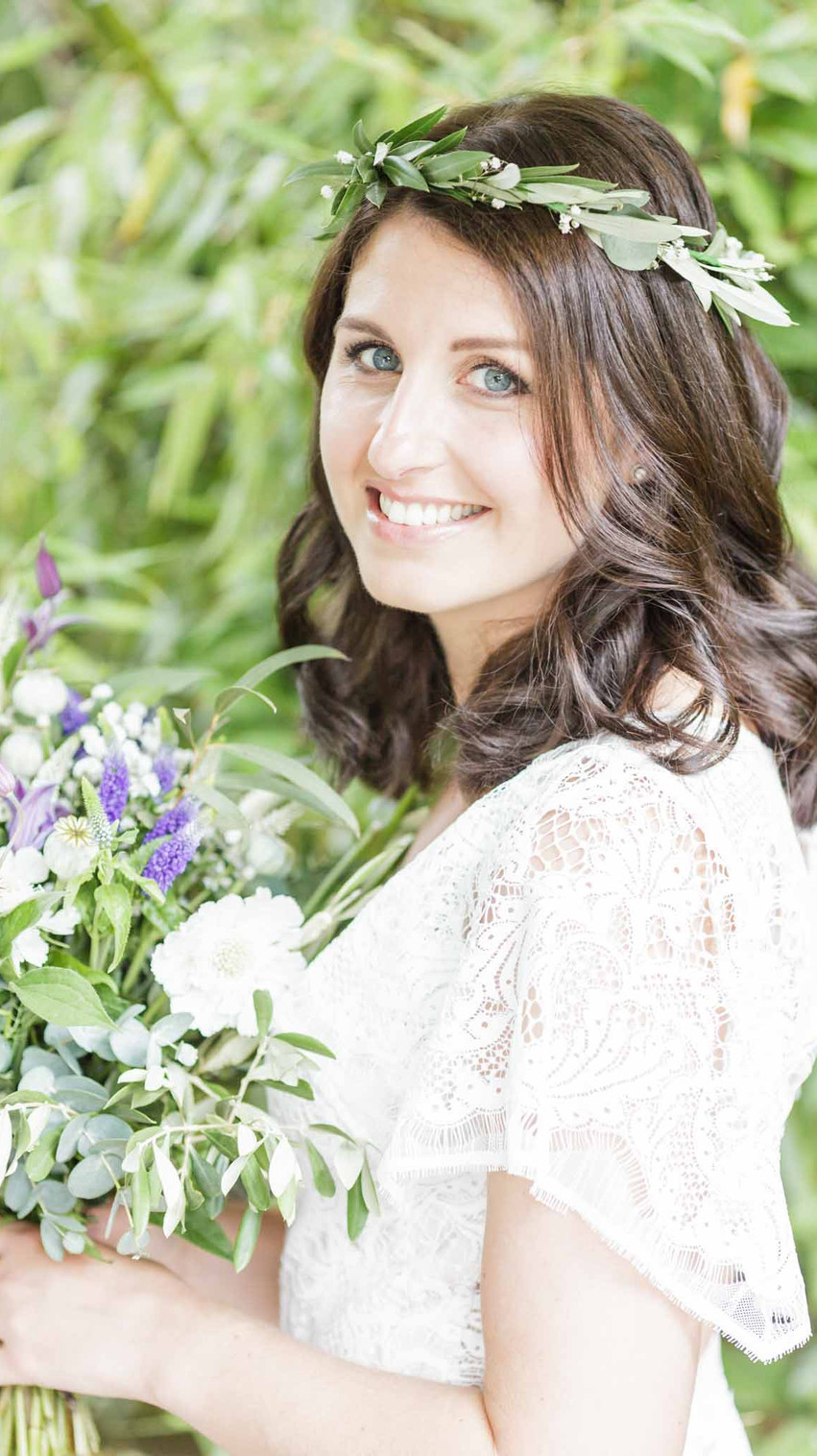 bride with a bouquet smiling for the camera in a garden