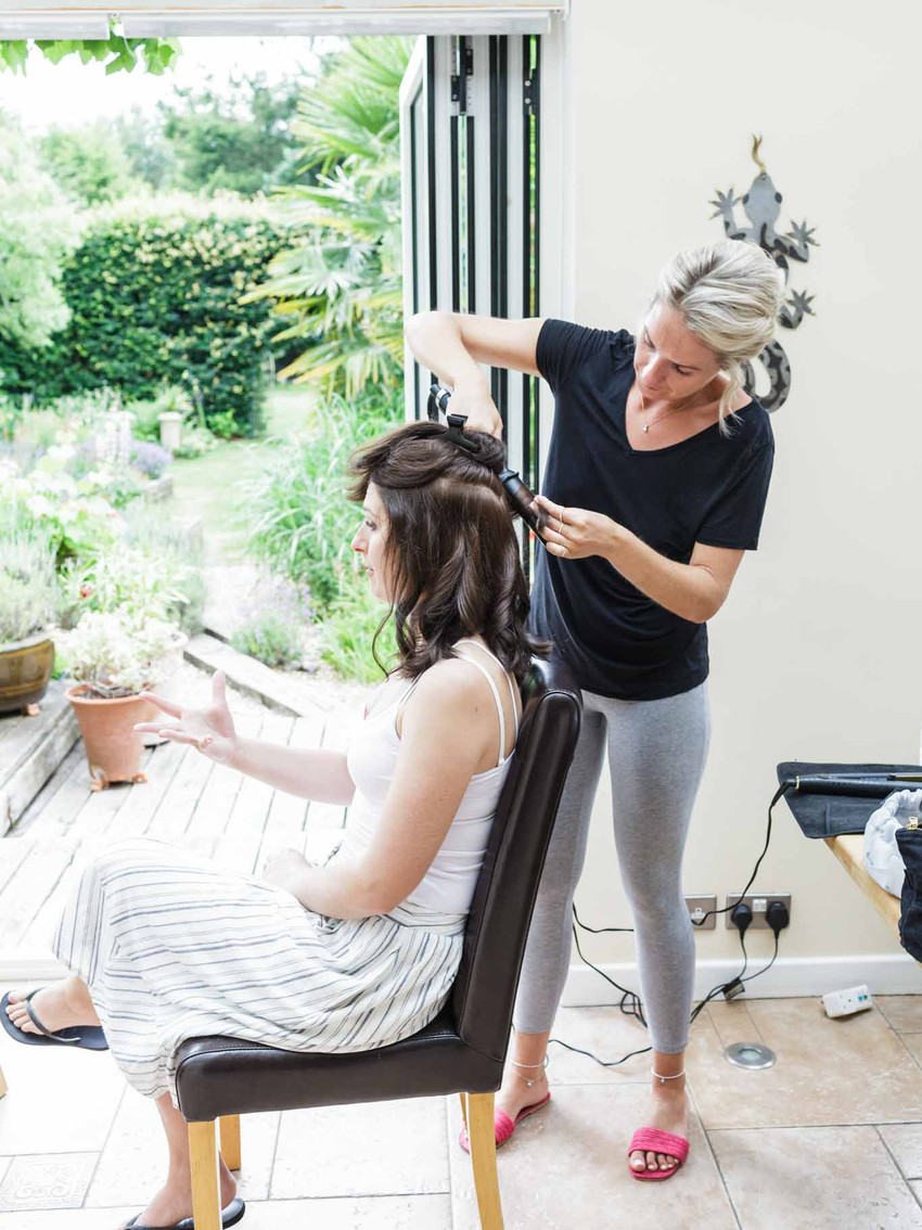 bride having her hair done sitting in a chair
