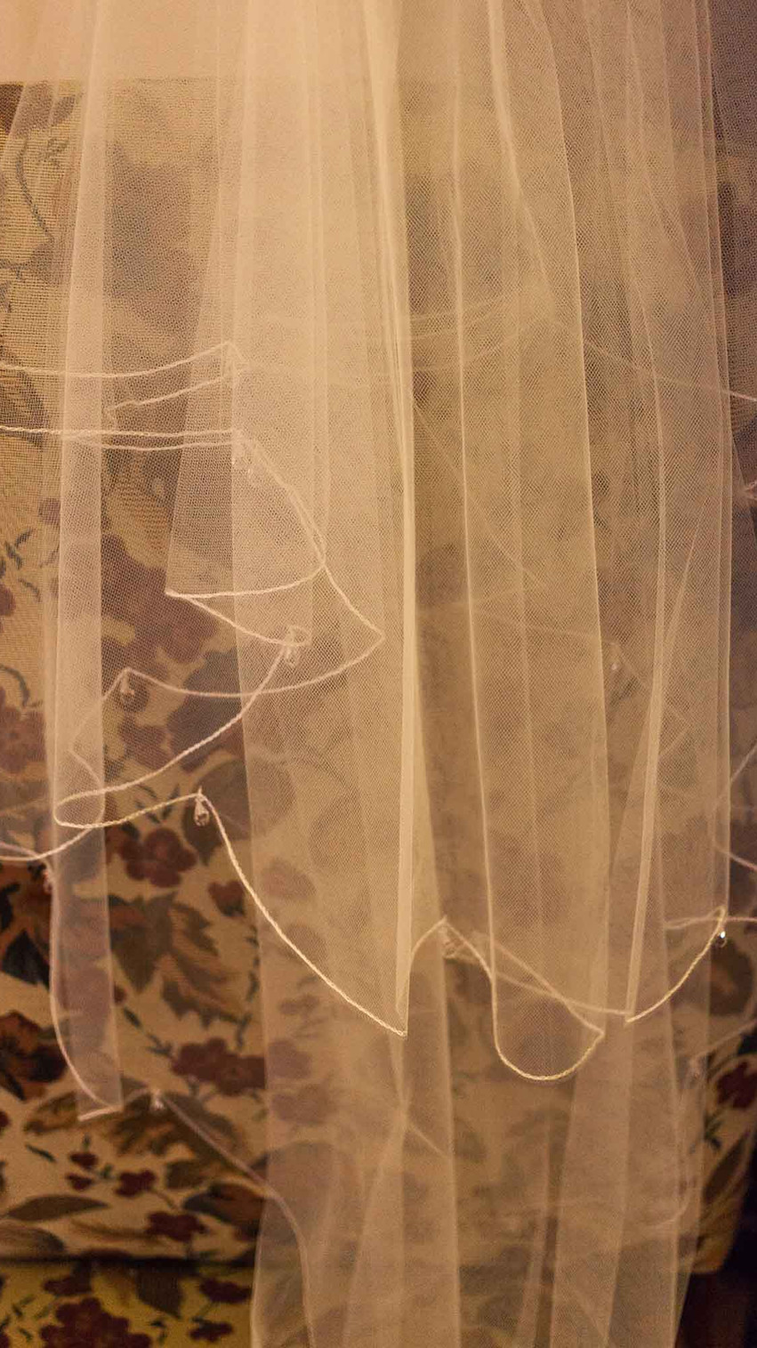 lace wedding dress hanging on a door