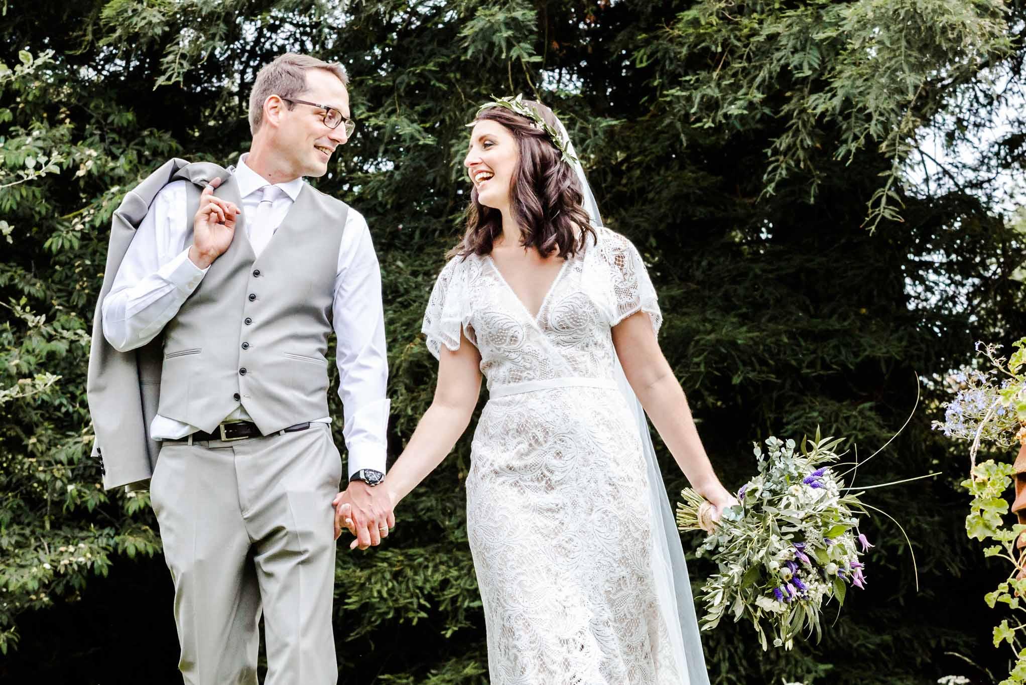 bride and groom walking hand in hand in a garden