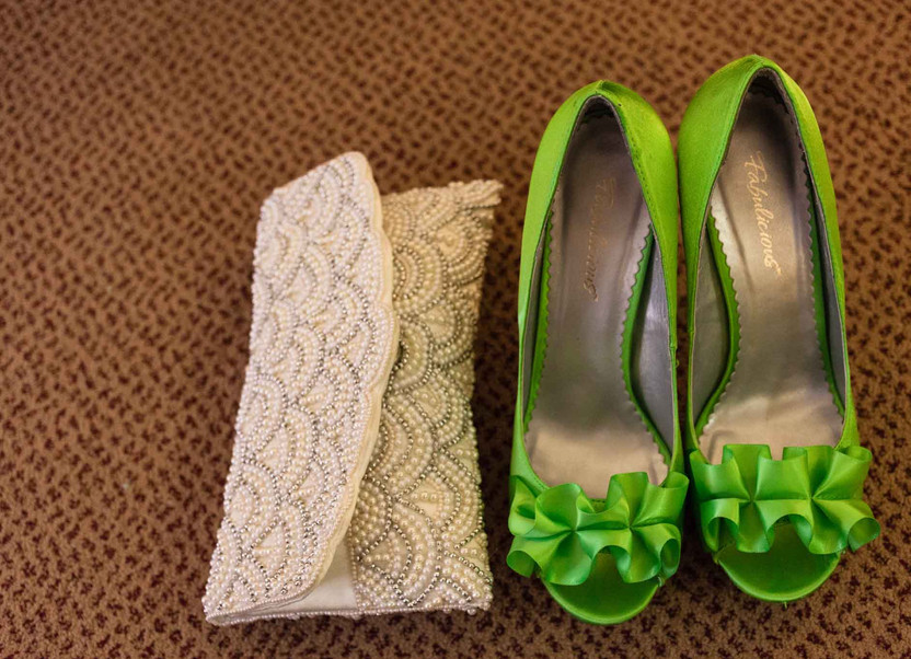 gold clutch bag next to some green shoes on a brown carpet