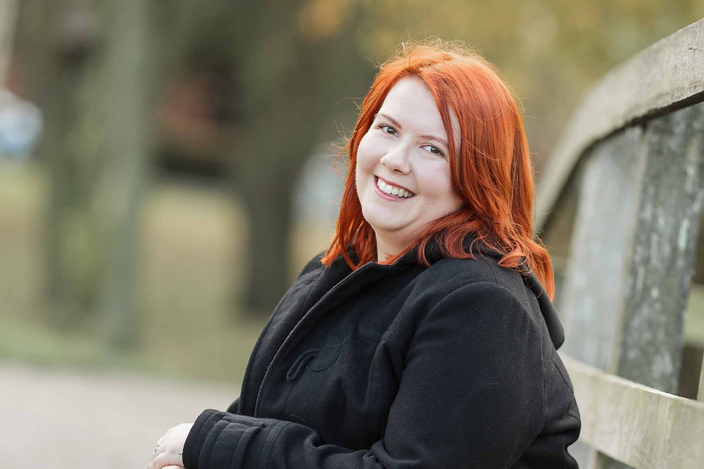 red haired woman in a black coat sitting on a wooden bridge