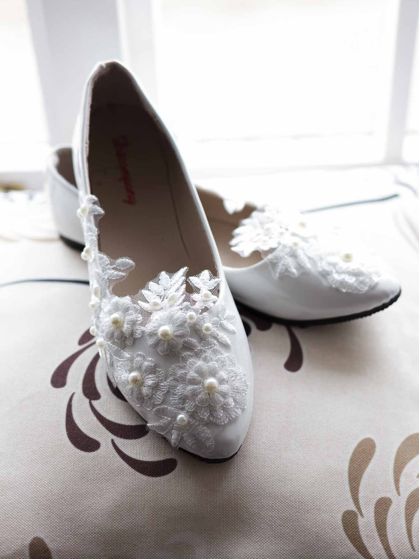 white wedding shoes on a window sill