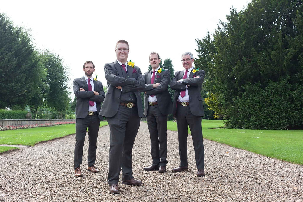 groomsman standing arms folded on a path