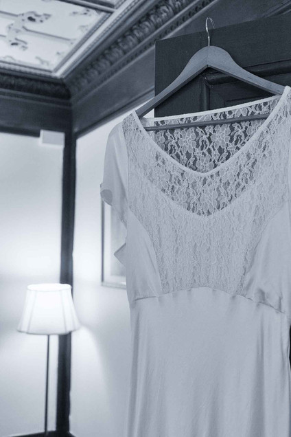 white lace wedding dress hung on a door