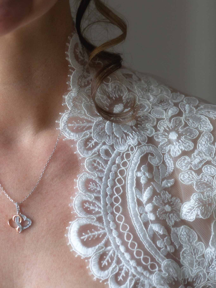 lclose up of a bride wearing a lace wedding dress and silver necklace