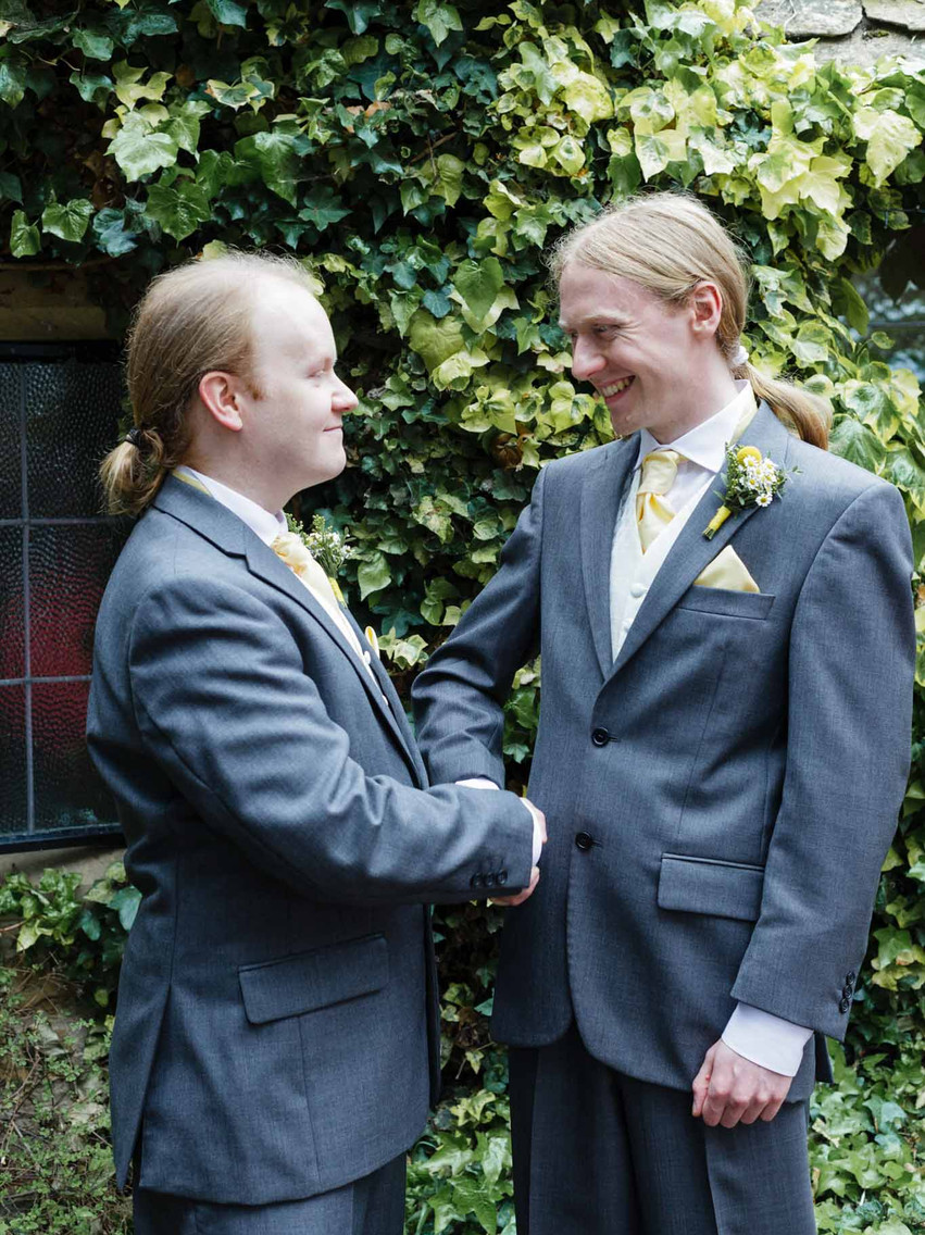groom and best man shaking hands in front of some trees