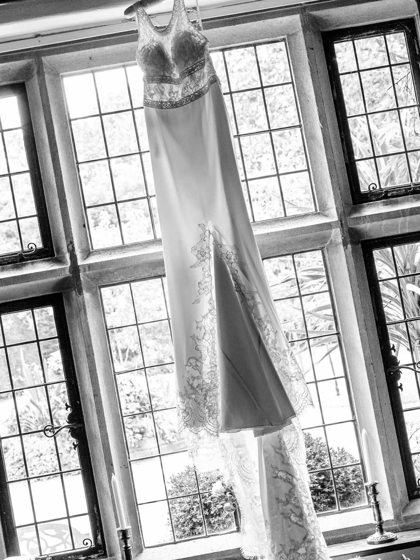 white wedding dress hanging in front of a stained glass window