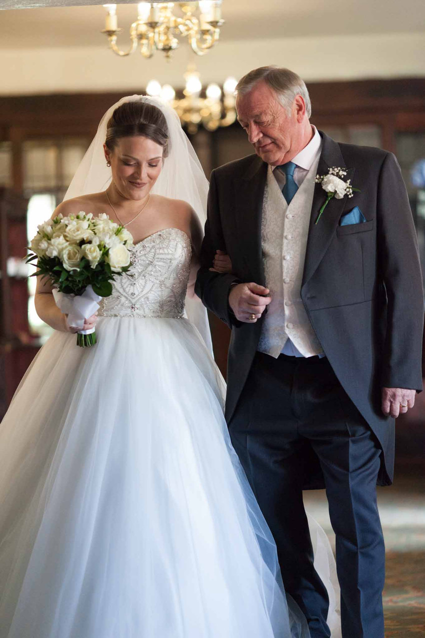 A father ecorts his daughter down the aisle on her wedding day
