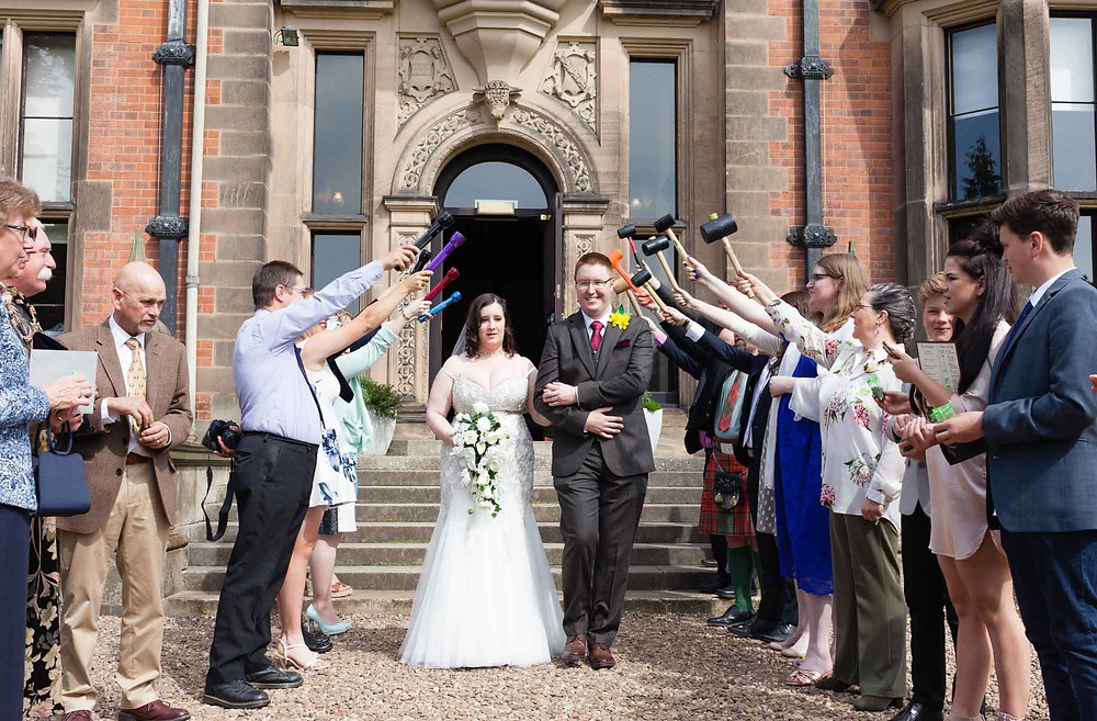 bride and groom walking beneath a guard of honour in the sunshine