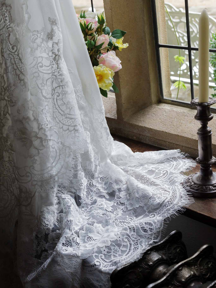 wedding dress hanging in front of a window by a candlestick