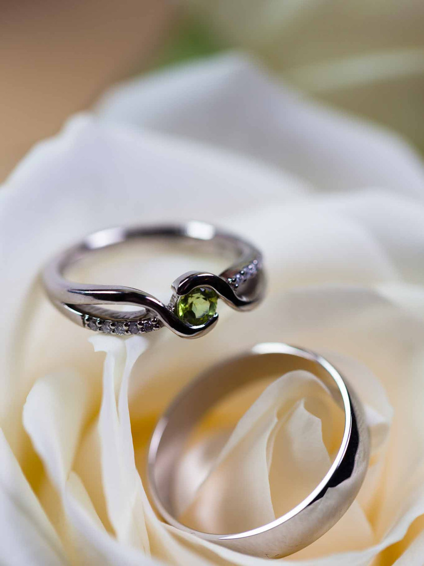 wedding rings resting on a white flower
