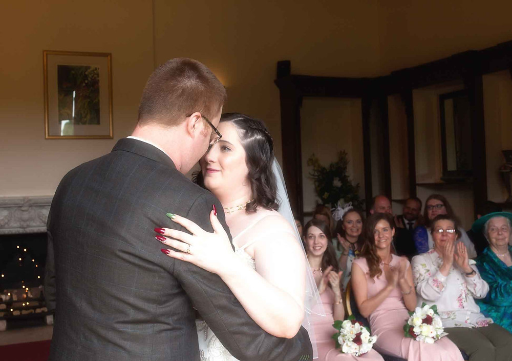bride and groom embrace at the altar