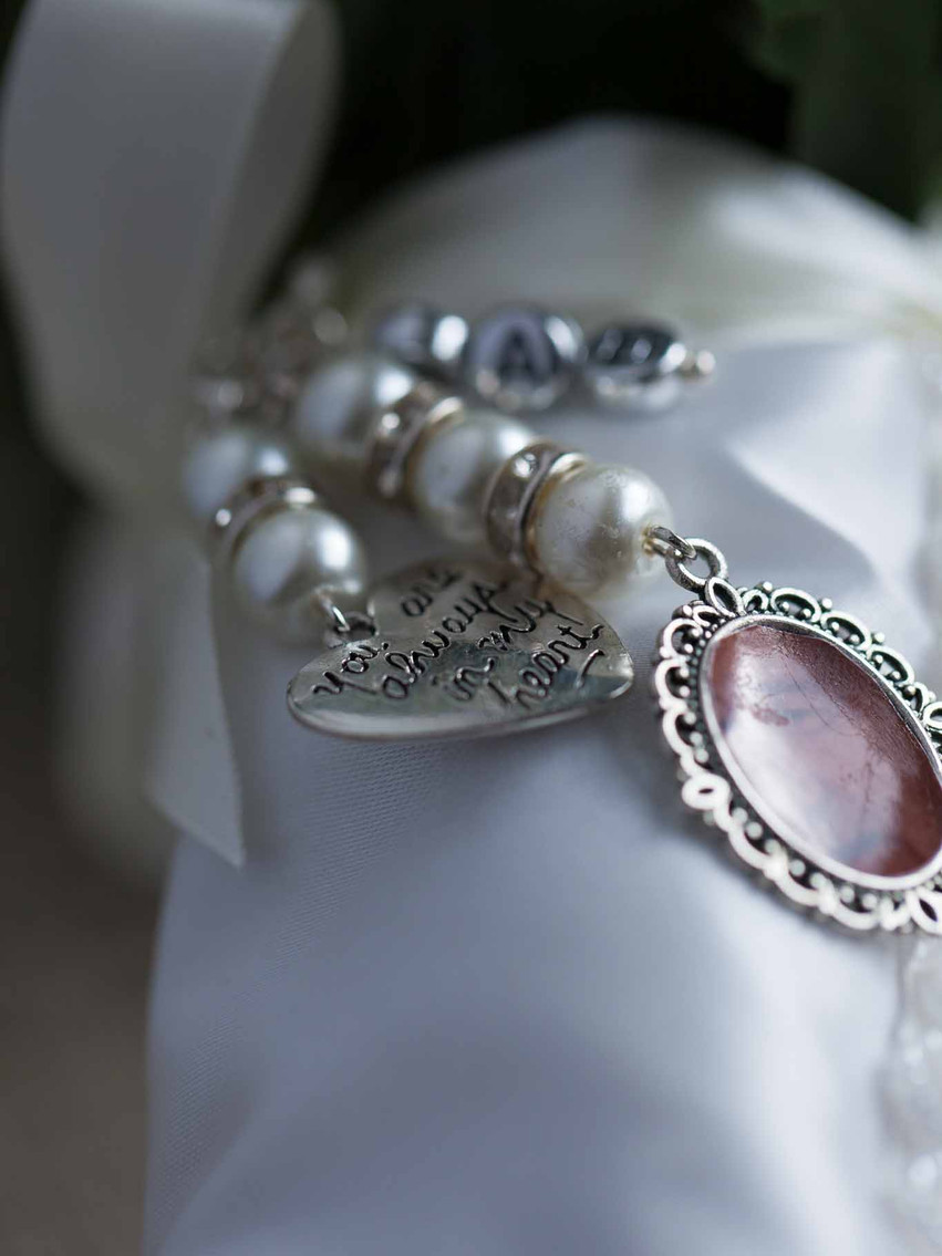 silver bracelet with a ruby insert on a silk pillow