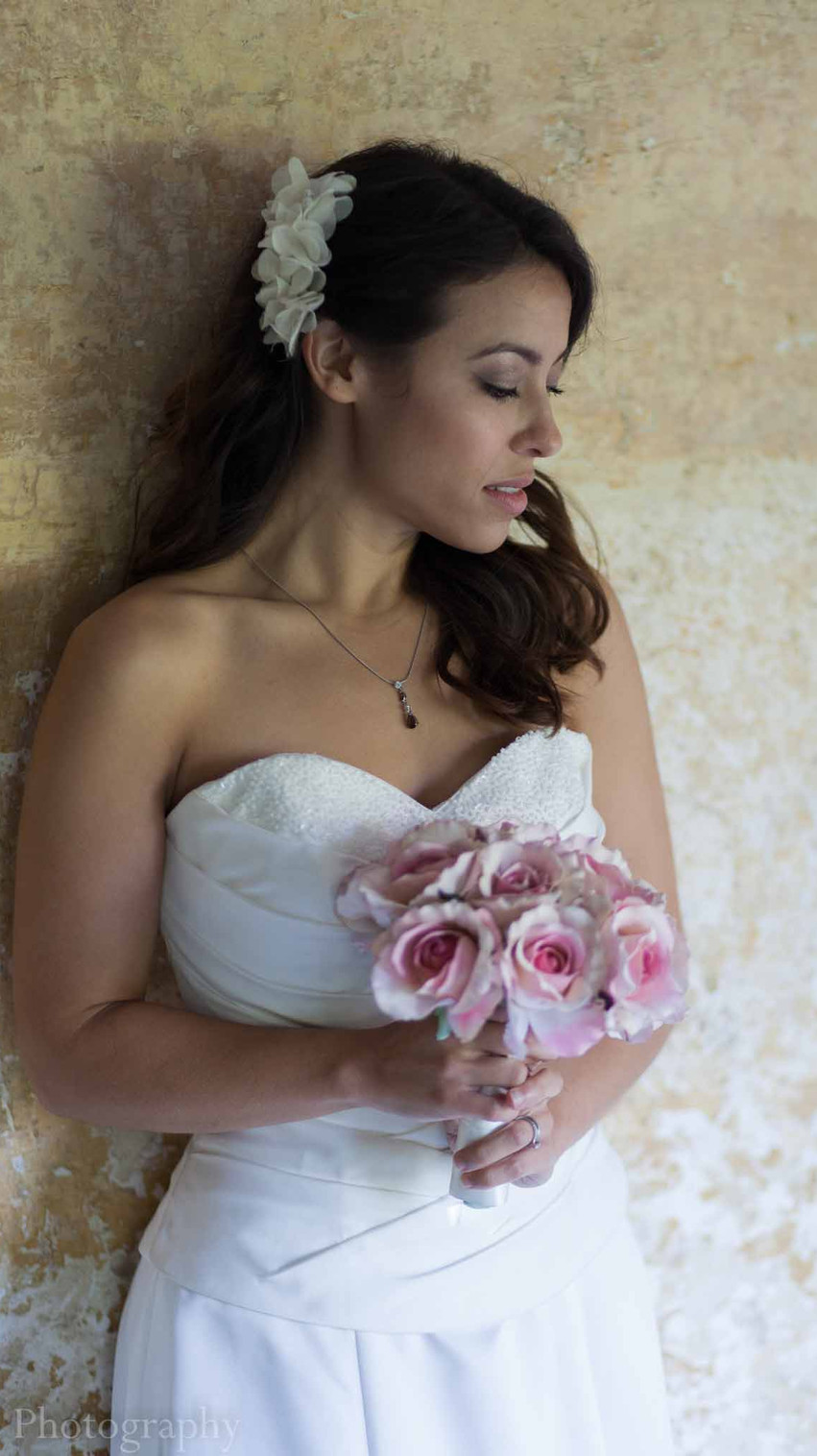 bride in her wedding dress against a yellow wall holding a bouquet of pink flowers