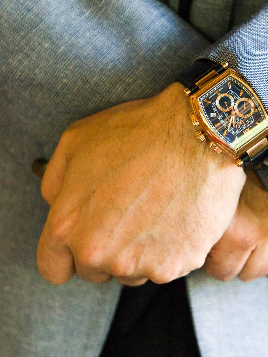 close up of a mans watch with a gold face and black strap