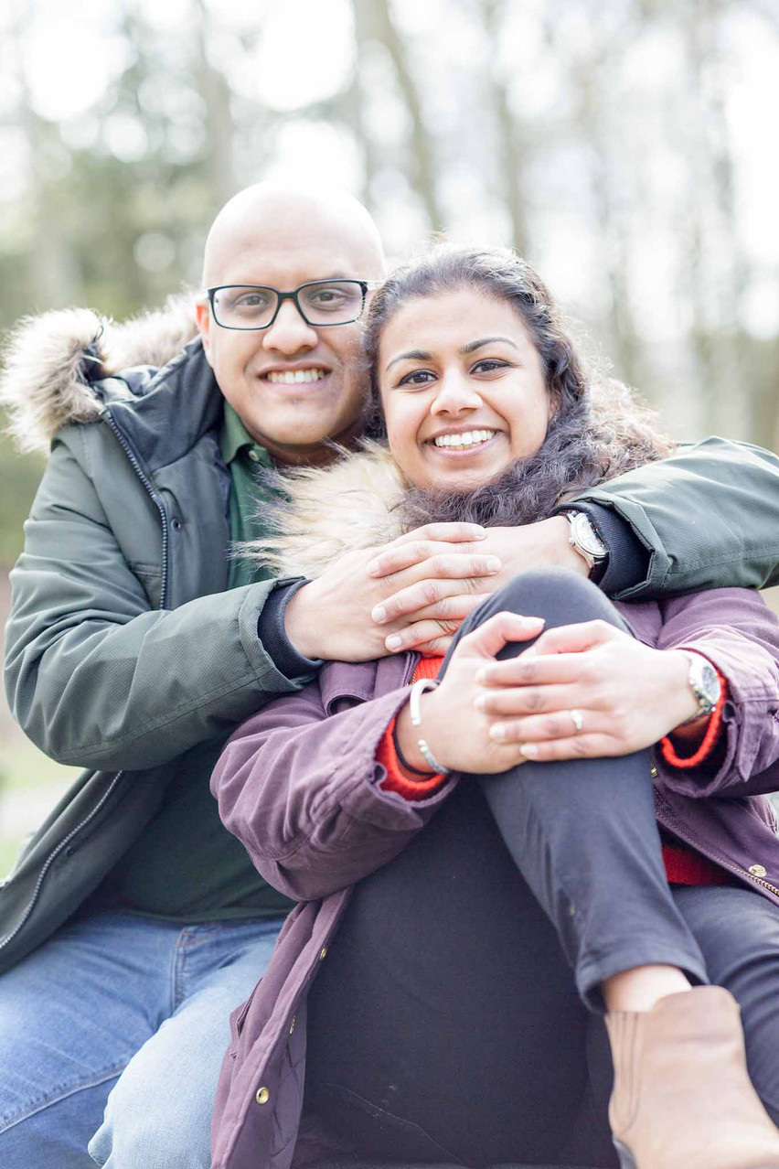 couple arm in arm sitting on a park bench