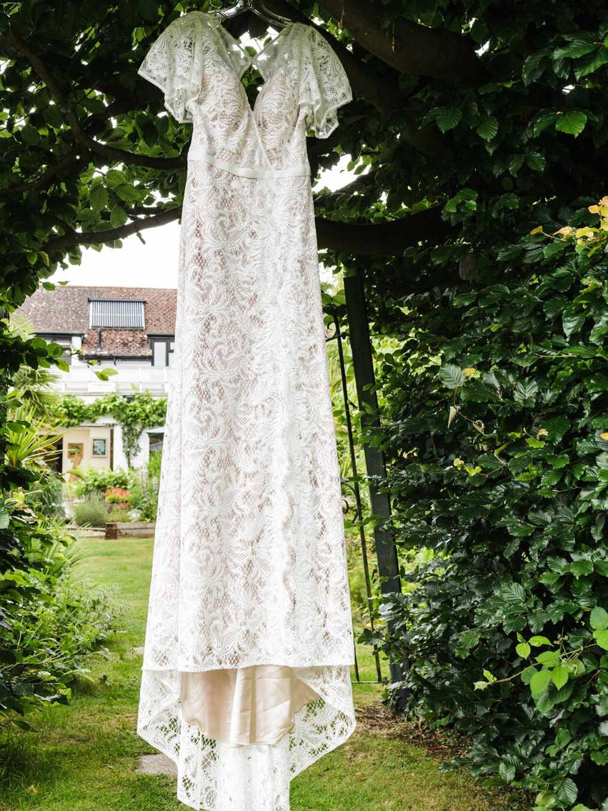 white wedding dress hanging in a garden