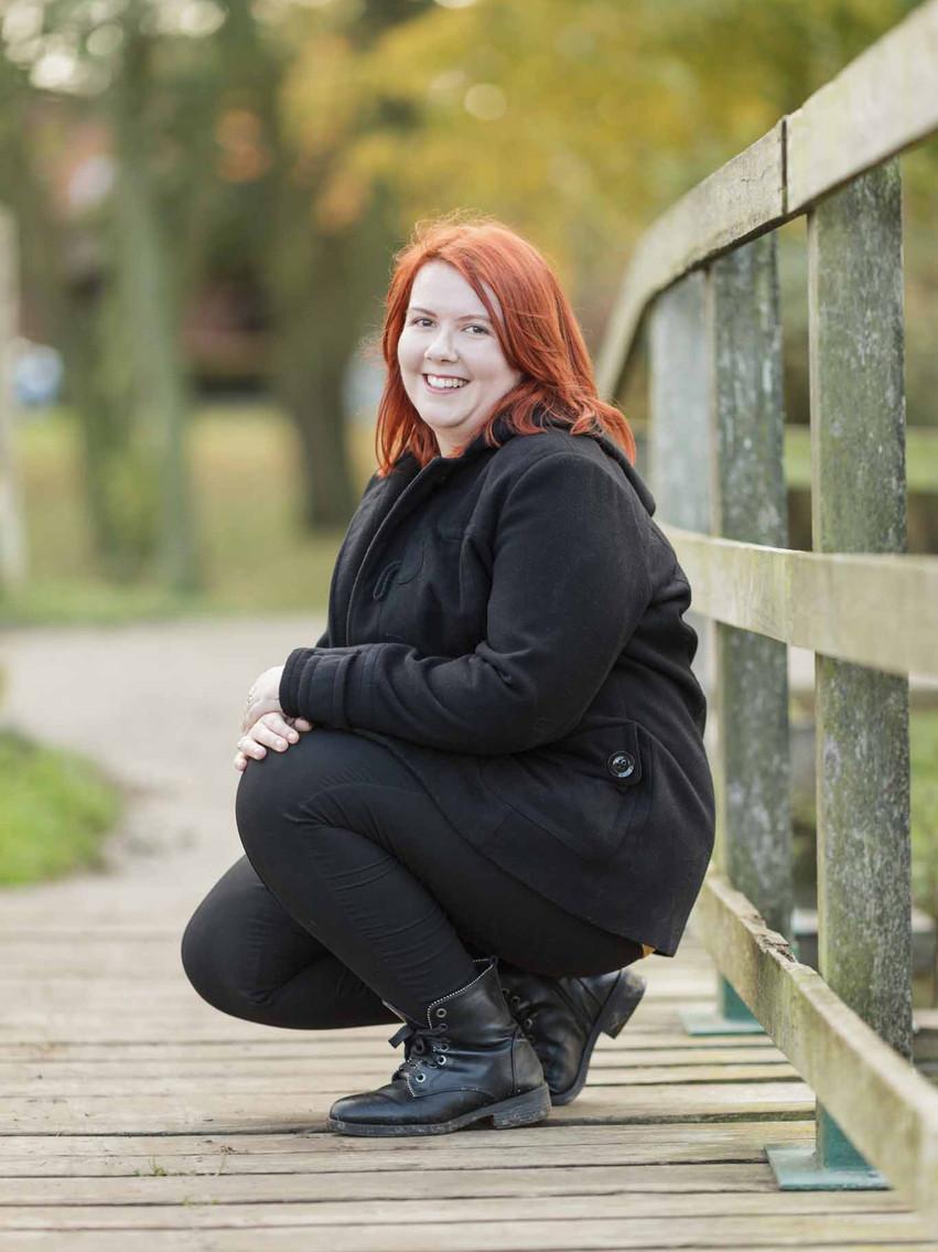 woman sitting down on a wooden bridge