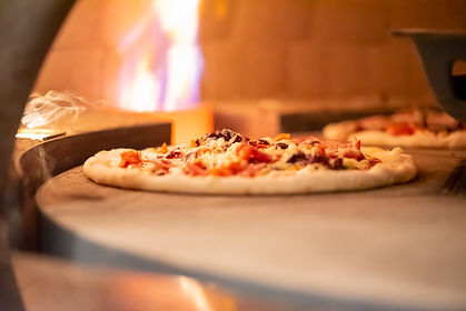 A pizza just starting to bake in Johannsons wood-fired piza oven