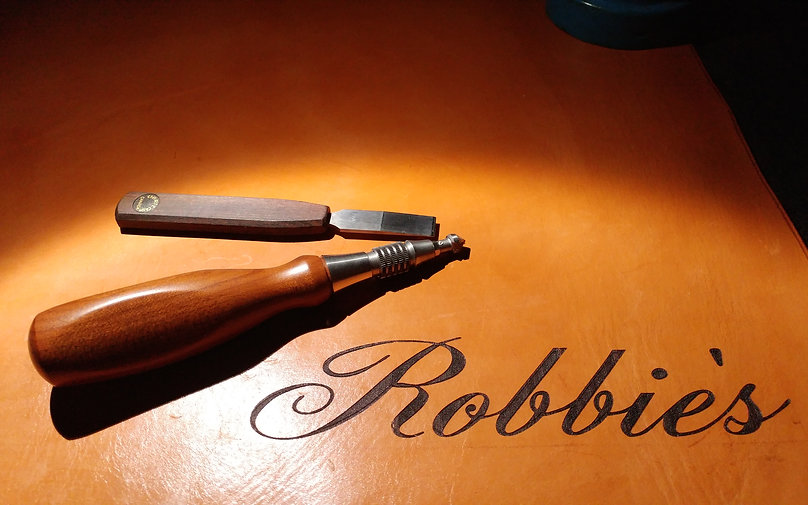 This is a photo of Robbies Instrument Repair logo on his musical instrument repair bench pad in Vernon BC.