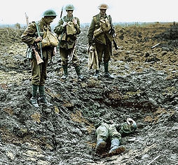1917 three british soldiers stand looking at the body of a fallen comrade
