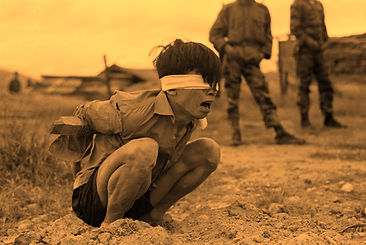 A Viet Cong prisoner captured in 1967 by the U.S. Army awaits interrogation. He has been placed in a stress position by tying a board between his arms.