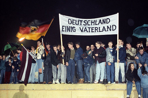 """The fall of the wall was the start of the true push for reunification of the country, as demonstrated by this group of Berlin citizens holding a German flag and a poster reading Deutschland Einig Vaterland (""""Germany United Fatherland"""")."""
