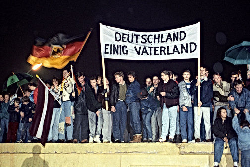 "The fall of the wall was the start of the true push for reunification of the country, as demonstrated by this group of Berlin citizens holding a German flag and a poster reading Deutschland Einig Vaterland (""Germany United Fatherland"")."