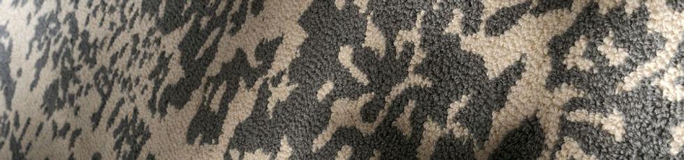 Tappeto tuftato a mano in lana. Matrix è una caduta di segni che diventa un tappeto. Una superficie senza verso né direzione, accostabile all'infinito come un pavimento corroso.