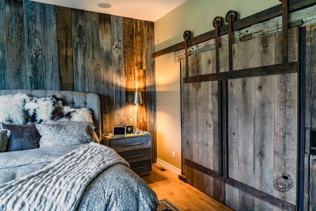 Reclaimed wood wall and sliding barn door with rustic custom steel hardware