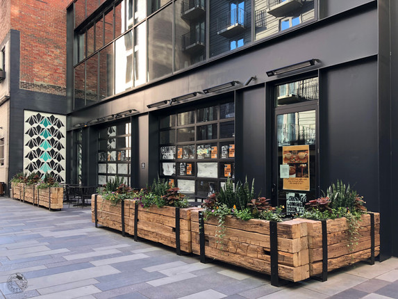 Reclaimed barn beam planter boxes with steel strapping, featured at Dairy Block -- a unique micro-district in the heart of Denver's historic LoDo neighborhood.
