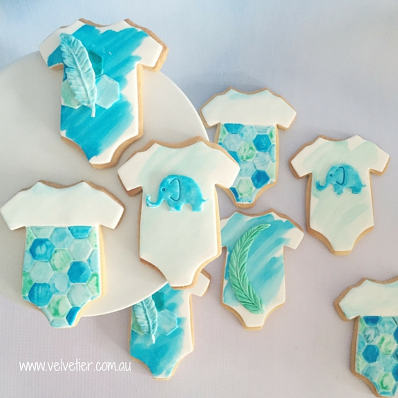 Shades of Blue baby onsie cookies with hexagons feathers and elephants Velvetier custom cookies Bris