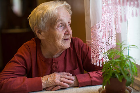 An elderly woman looks out the window..j
