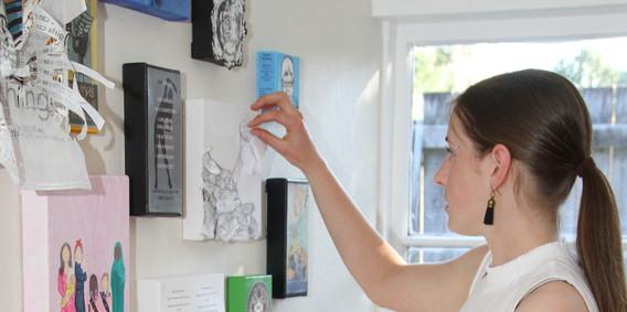 Ella adjusting her artwork