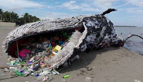 An art installation depicting a beached whale whose body is filled with plastic waste