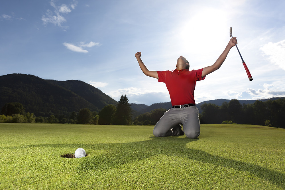 Professional young male golf player on knees and arms raised with putter in hand