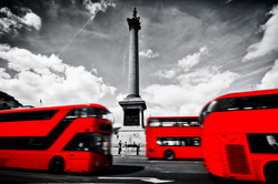 Red buses in motion on Trafalgar Square