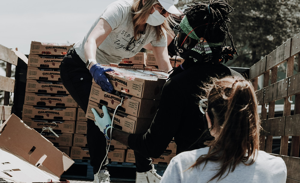 Young adults unloading boxes from a truck