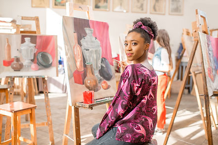 Portrait of a young african student sitting with still life painting at the studio.jpg