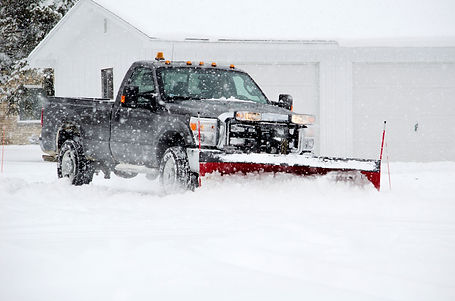 a worker plows heavy white snow during a