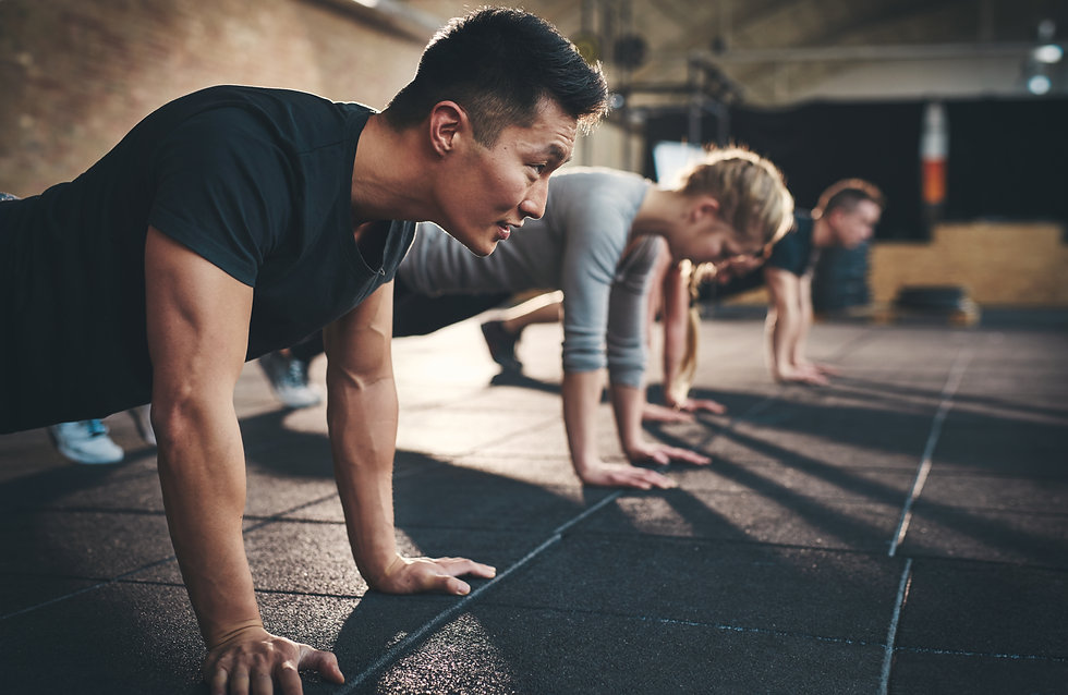 Fit young people doing pushups in a gym